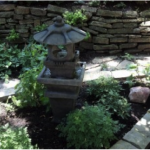 A fountain's beautiful trickling sound fills up a garden space.